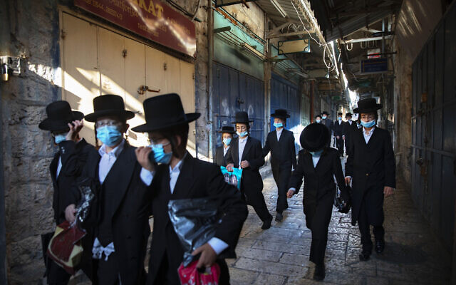 A group of ultra-Orthodox Jewish youth wear protective face masks following government measures to help stop the spread of the coronavirus, as they walk in Jerusalem's Old City, July 16, 2020. (AP/Oded Balilty)