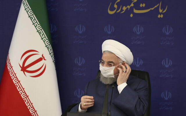 In this photo released by the official website of the office of the Iranian Presidency, President Hassan Rouhani adjusts his face mask in a meeting of the national headquarters of the fight against the COVID-19, in Tehran, Iran, July 18, 2020 (Iranian Presidency Office via AP)