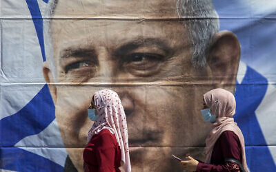 Muslim women wearing face masks walk past a poster hung by supporters of Prime Minister Benjamin Netanyahu outside the District Court in Jerusalem, July 19, 2020 (AP Photo/Ariel Schalit)