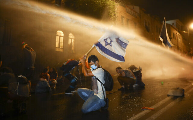 Police use a water cannon against demonstrators during a protest against Prime Minister Benjamin Netanyahu in Jerusalem, on July 18, 2020 (AP Photo/Oded Balilty)