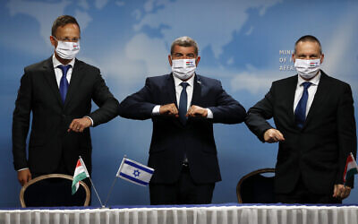 Israeli Foreign Minister Gabi Ashkenazi, center, his Hungarian counterpart Peter Peter Szijjártó, left and Israeli Minister of Science and Technology Izhar Shay, right, give elbow bump greetings during their meeting, in Jerusalem, July 20, 2020. (Ronen Zvulun/Pool via AP)