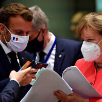 German Chancellor Angela Merkel, right, speaks with French President Emmanuel Macron, left, during a round table meeting at an EU summit in Brussels, July 20, 2020 (John Thys, Pool Photo via AP)