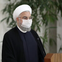 Iranian President Hassan Rouhani wears a protective face mask to help prevent spread of the coronavirus as he gives a press briefing in Tehran, Iran, July 21, 2020. (Iranian Presidency Office via AP)