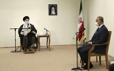 Iranian Supreme Leader Ayatollah Ali Khamenei, left, speaks with Iraqi Prime Minister Mustafa al-Kadhimi as they wear protective face masks to help prevent spread of the coronavirus, during their meeting in Tehran, Iran, July 21, 2020. (Office of the Iranian Supreme Leader via AP)