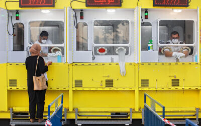 A woman is tested by a healthcare worker for the coronavirus at a mobile testing station, in east Jerusalem, July 21, 2020. (AP Photo/Oded Balilty)