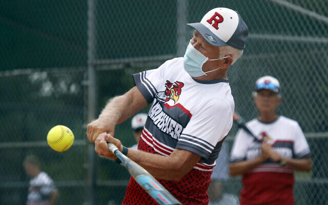 Amid concerns of the spread of COVID-19, Rick McAll, 73, wears a mask as he hits during a senior's softball game in Richardson, Texas, Tuesday, July 21, 2020. (AP Photo/LM Otero)