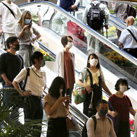 People wearing face masks to protect against the spread of the new coronavirus take an escalator at Yokohama station near Tokyo, July 22, 2020. (AP Photo/Koji Sasahara)