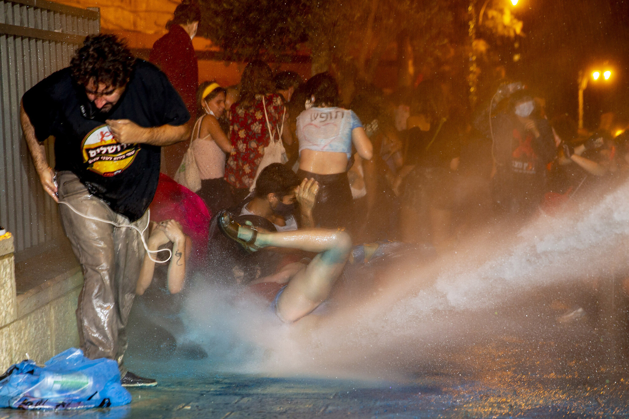 Police use a water cannon to disperse demonstrators during a protest against Prime Minister Benjamin Netanyahu outside his residence in Jerusalem, July 22, 2020 (AP Photo/Ariel Schalit)