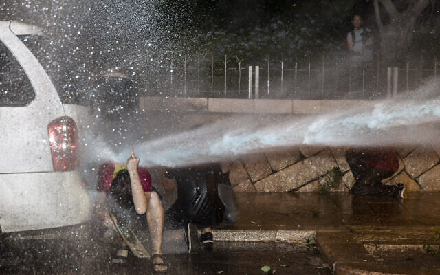 Police use a water cannon to disperse demonstrators during a protest against Israel's Prime Minister Benjamin Netanyahu outside his residence in Jerusalem, early Friday, July 24, 2020.  (AP/Ariel Schalit)