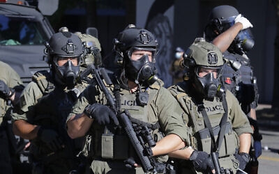 Law enforcement officers hold weapons as police clash with protesters, July 25, 2020, during a Black Lives Matter protest near the Seattle Police East Precinct headquarters in Seattle (AP Photo/Ted S. Warren)