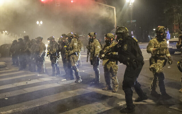 Federal officers line up to deploy tear gas at demonstrators during a Black Lives Matter protest at the Mark O. Hatfield United States Courthouse July 26, 2020, in Portland, Oregon. (AP Photo/Marcio Jose Sanchez)