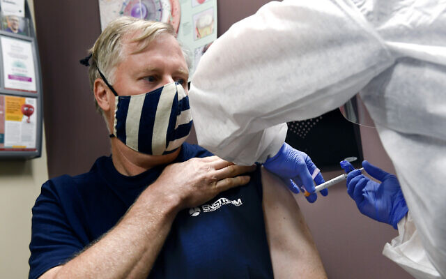 A nurse gives a volunteer an injection, as the world's biggest study of a possible COVID-19 vaccine, developed by the US National Institutes of Health and Moderna Inc., gets underway on July 27, 2020, in Binghamton, NY. (AP Photo/Hans Pennink)