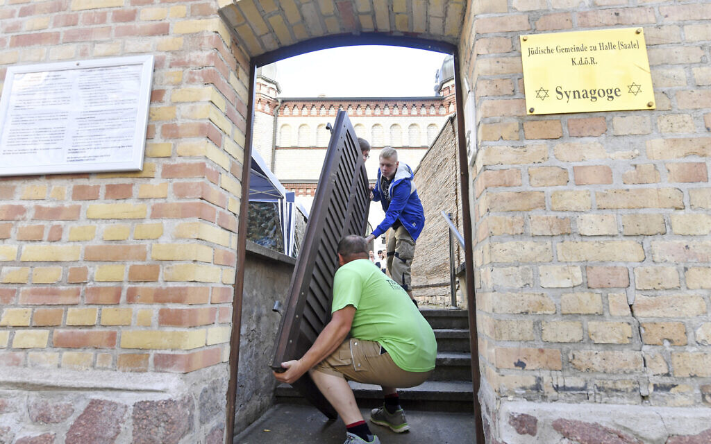 Carpenter Thomas Thiele, front, removes the bullet hole-ridden door of a synagogue in Halle, Germany, July 28, 2020. (Hendrik Schmidtpa/dpa via AP)