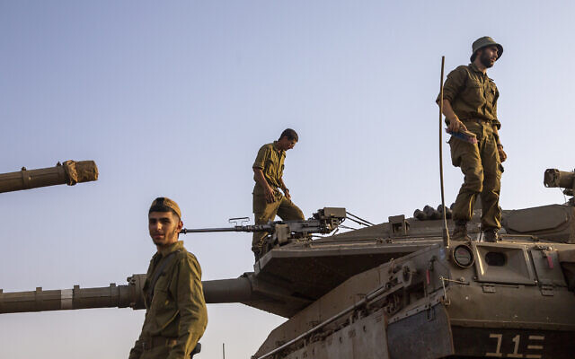 Israeli soldiers work on tanks near the Lebanon border on July 28, 2020. (AP Photo/Ariel Schalit)