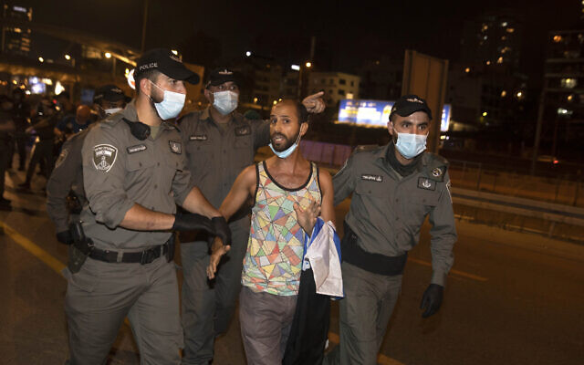 An Israeli protester is detained after blocking a main highway during a protest against corruption near the house of Israel's Minister of Public Security in Tel Aviv, Israel, Tuesday, July 28, 2020. (AP Photo/Sebastian Scheiner)