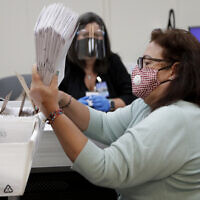 Illustrative: Miami-Dade County Department of Elections employee Elizabeth Prieto gathers vote-by-mail ballots for the August 18 primary election as the canvassing board meets to verify ballot signatures at the Miami-Dade County Elections Department, July 30, 2020, in Doral, Florida. (AP Photo/Lynne Sladky)
