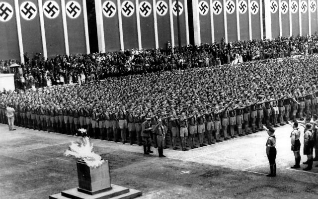 German Nazi soldiers line up at attention during the opening ceremonies of the XI Summer Olympic Games at the Lustgarten in Berlin, Germany on Aug. 1, 1936. The lighted Olympic torch is in the foreground. (AP Photo)