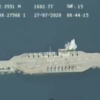 In video released on July 28, 2020, an explosion is seen next to a mock US aircraft carrier in the Strait of Hormuz during military exercises held by Iran's Islamic Revolutionary Guard Corps. (Screen capture: Twitter)