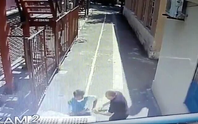 Screen capture from video of a security guard outside a synagogue in Ukraine struggling with an ax-wielding attacker, July 28, 2020. (Twitter)