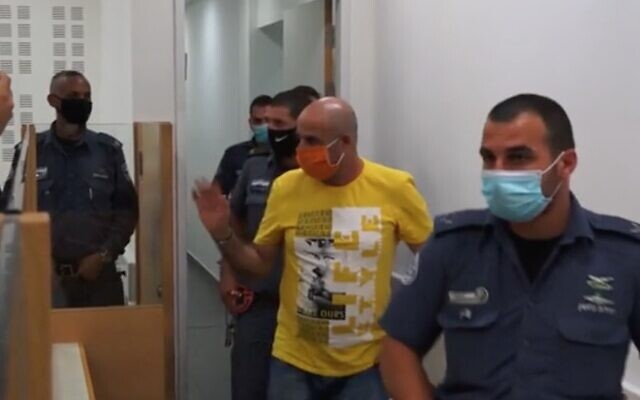 Screen capture from video of David Chaim, center, arrives at the Central District Court for the verdict in his trial for the murder of his ex-wife, Ofira, July 12, 2020. (Ynet)