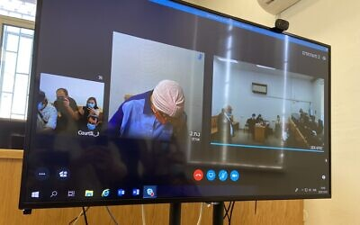 Malka Leifer (C) refuses to raise her head while appearing over Skype during an extradition hearing at the Jerusalem District Court on July 20, 2020. (Jacob Magid/Times of Israel)