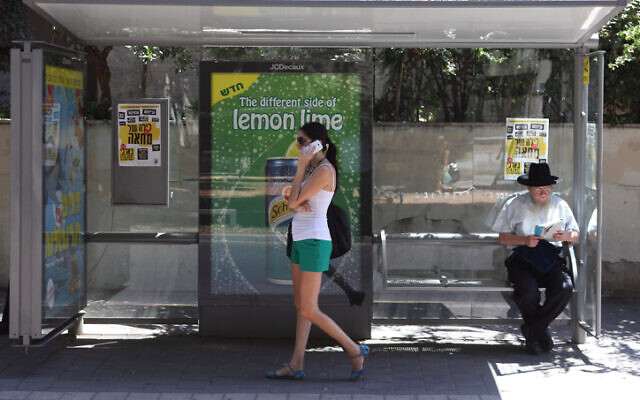 Illustrative: A woman talks on her mobile phone at a bus stop, in Tel Aviv, on August 24, 2012. (Yaakov Naumi/Flash90/File)