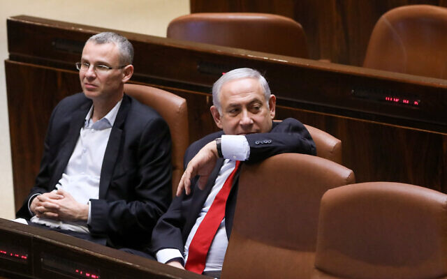 Prime Minister Benjamin Netanyahu, right, with then-tourism minister Yariv Levin during a vote at the assembly hall of the Knesset on February 13, 2018. (Yonatan Sindel/Flash90/File)