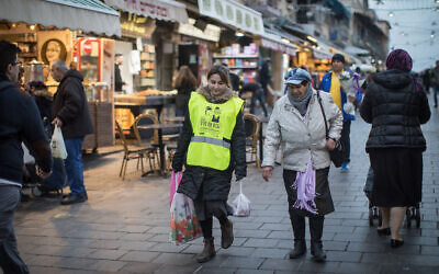 A young woman helps an elderly lady with her grocery bags at the Mahane Yehuda Market in Jerusalem, February 14, 2019. (Hadas Parush/Flash90)