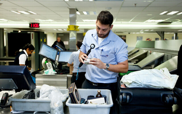 File photo of security personnel checking passengers' luggage at Ben Gurion International Airport in Lod, September 7, 2019. (Moshe Shai/Flash90)