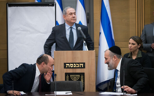 Prime Minister Benjamin Netanyahu speaks as then-defense minister Naftali Bennett and Interior Minister Aryeh Deri confer, during a meeting of right-wing party leaders at the Knesset following election day, on March 4, 2020. (Yonatan Sindel/Flash90)