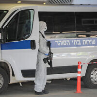 Prison guards wearing protective clothing as a preventive measure against the coronavirus, seen as they transport a prisoner suspected of having the coronavirus at Shaare Zedek Medical Center in Jerusalem on March 30, 2020. (Yossi Zamir/Flash90)