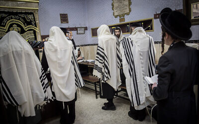 Ultra-Orthodox men pray at a synagogue in the neighborhood of Mea Shearim, Jerusalem, on May 20, 2020 (Yonatan Sindel/Flash90)