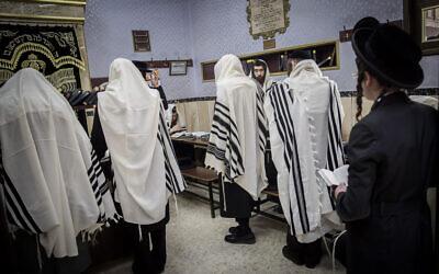 Ultra-Orthodox men pray at a synagogue in the neighborhood of Mea Shearim, Jerusalem, on May 20, 2020 (Yonatan Sindel/Flash90)