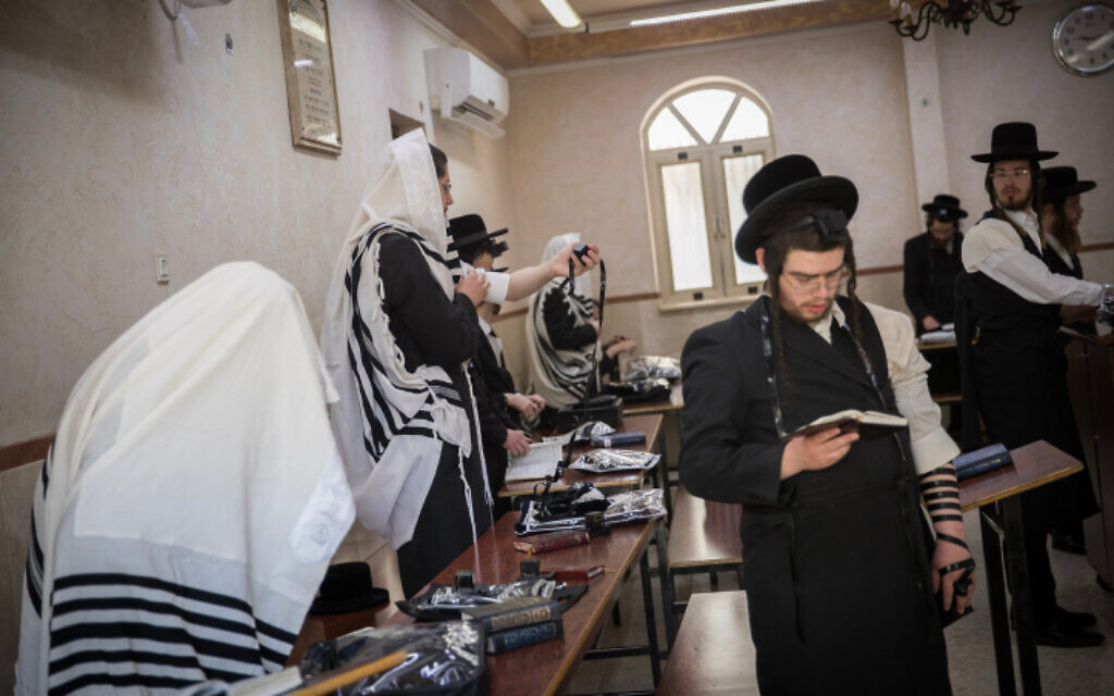 Ultra Orthodox Jewish men eschew masks while praying at a synagogue in Jerusalem on May 20, 2020. (Yonatan Sindel/Flash90)