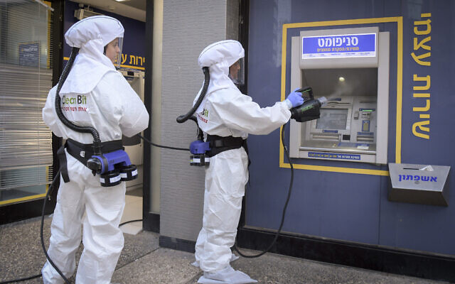 Cleaners in protective gear disinfect an ATM at a bank in Ramat Gan on June 3, 2020. (Flash90)