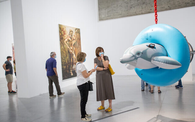 Visitors wear protective face masks at the Jeff Koons exhibition at the Tel Aviv Museum of Art, June 3, 2020; the museum will reopen December 1, 2020 after being closed since September 18, due to the coronavirus (Miriam Alster/Flash 90)