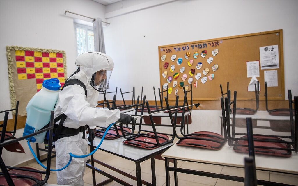 Cleaning workers disinfect a classroom at the Gymnasia Rehavia high school in Jerusalem on June 3, 2020. (Yonatan Sindel/ Flash90)