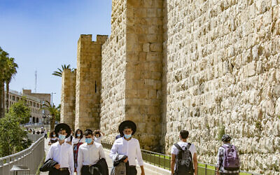 Jerusalemites wearing protective mask walk near the Jaffa Gate of the Old City of Jerusalem on June 23, 2020. (Olivier Fitoussi/Flash90)