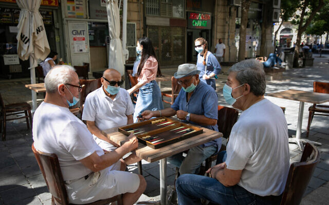 Jerusalemites wearing face masks play backgammon in Jerusalem on June 30, 2020. (Olivier Fitoussi/Flash90)