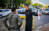 Police officers guard at the entrance to a neighborhood in the southern city of Ashdod, July 2, 2020, during a closure on some neighborhoods in the city following the spread of the coronavirus. (Flash90)