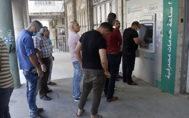 Illustrative: Palestinians wait in line at an ATM in the West Bank city of Nablus on July 2, 2020. (Nasser Ishtayeh/Flash90)