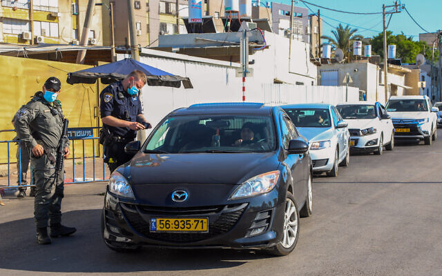 Police officers guard the entrance to a neighborhood in the city of Lod, July 2, 2020, during a closure (Yossi Aloni/Flash90)