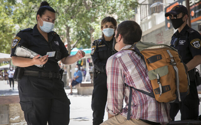 A man is given a fine by police officers for not wearing a mask in Jerusalem on July 3, 2020. (Olivier Fitoussi/Flash90)