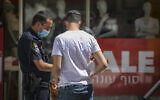 A Jerusalem man is fined by a police officer for failing to wear a face mask outside on July 03, 2020. (Olivier Fitoussi/Flash90)