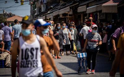 People wearing face masks as they shop at the Mahane Yehuda market in Jerusalem on July 3, 2020. (Yonatan Sindel/Flash90)