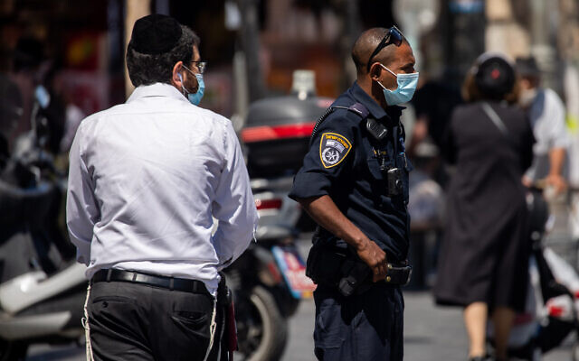 Police officers patrol outside the Mahane Yehuda market in Jerusalem to enforce the emergency regulations, on July 3, 2020. (Yonatan Sindel/Flash90)