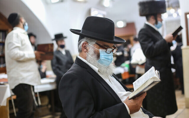 Jewish men pray with face masks at the burial site of Rabbi Shimon bar Yohai in Mount Meron, in northern Israel, July 4, 2020. (David Cohen/Flash90)