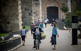 People walk wearing face masks walk near the Jaffa Gate outside Jerusalem's Old City on July 5, 2020. (Yonatan Sindel/Flash90)