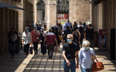 Illustrative: People wearing face masks walk and shop at the Mamilla mall near Jerusalem's Old City on July 6, 2020 (Olivier Fitoussi/Flash90)