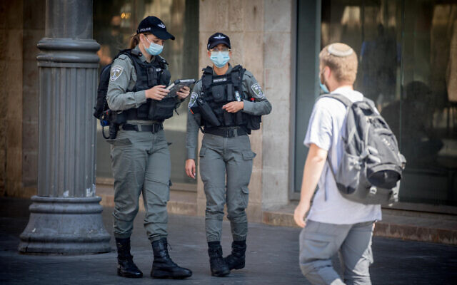 Israeli border police officers enforce mask regulations in central Jerusalem on July 6, 2020. (Yonatan Sindel/Flash90)